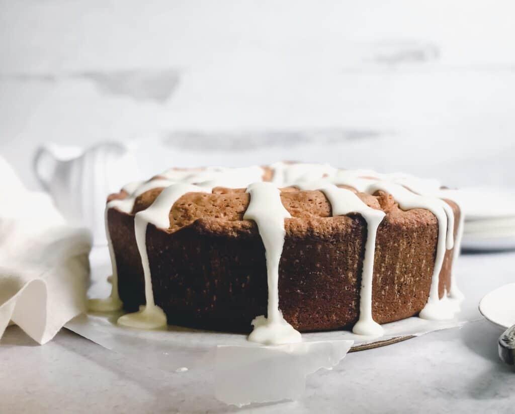 Whole pound cake with lemon glaze on gray surface
