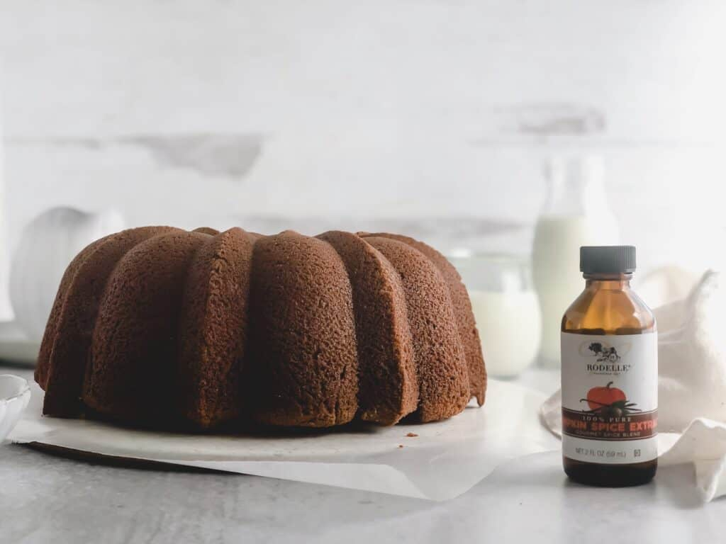 Pumpkin Spice Bundt Cake without glaze and bottle of Rodelle pumpkin spice extract on grey surface