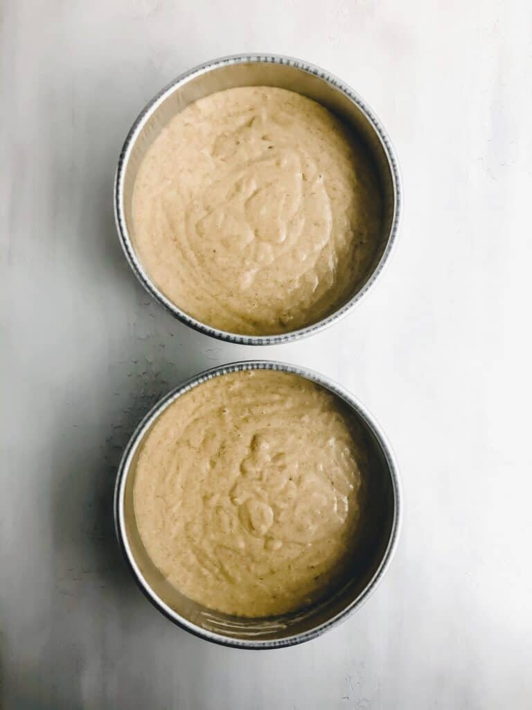cake batter in round cake pans on grey surface