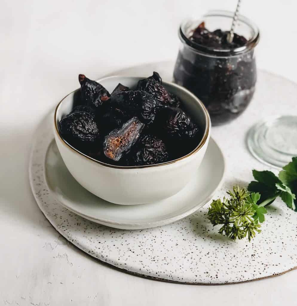 bowl of figs and fig jam on cake plate on grey surface