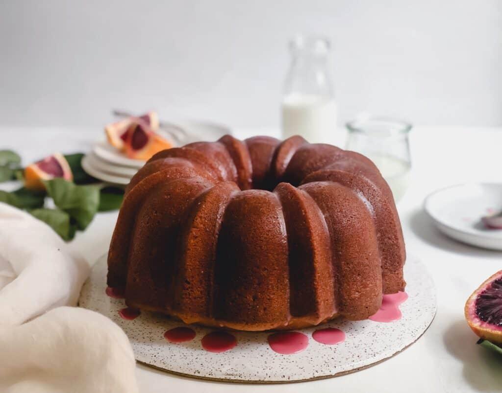whole blood orange cardamom bundt cake on cake place on gray surface