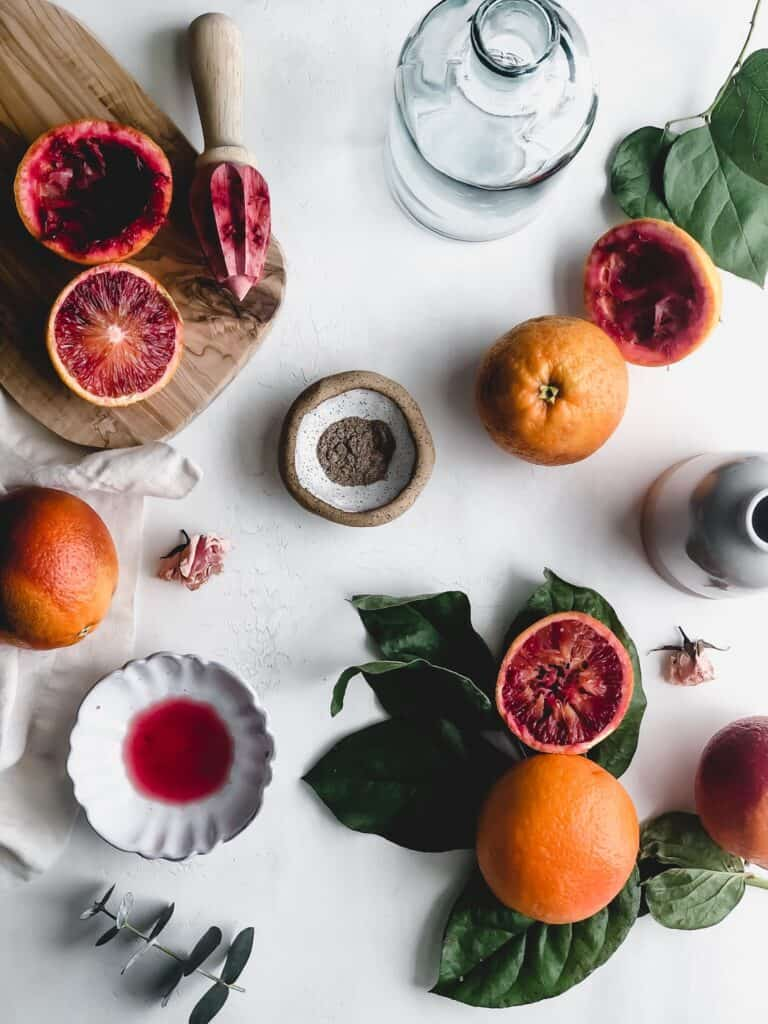 whole and sliced blood oranges with small bowl filled with cardamom and empty vases on gray surface