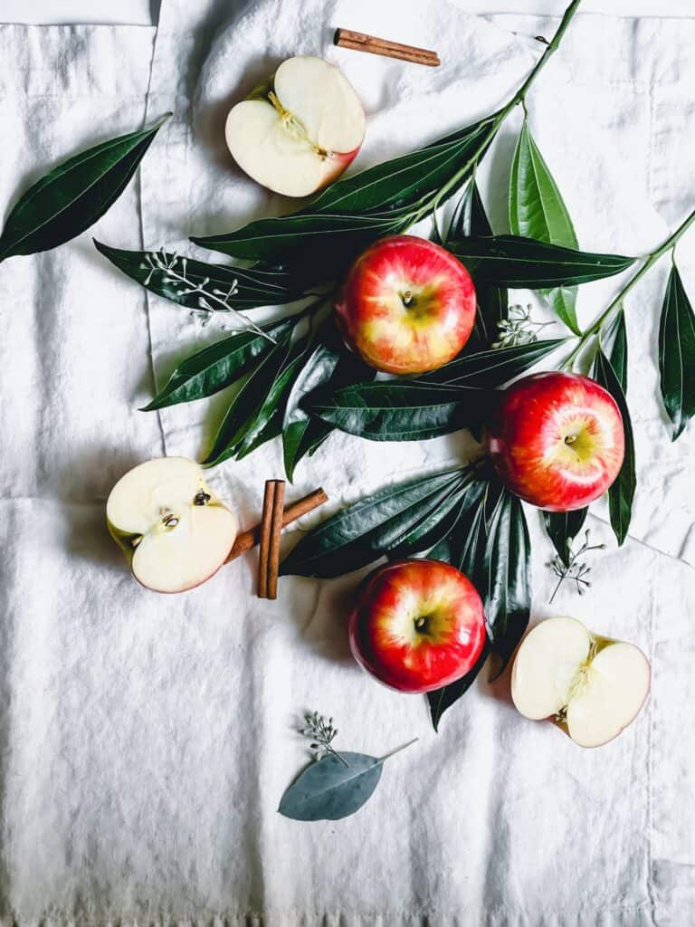 sliced and whole red apples, cinnamon sticks, and leaves on white surface